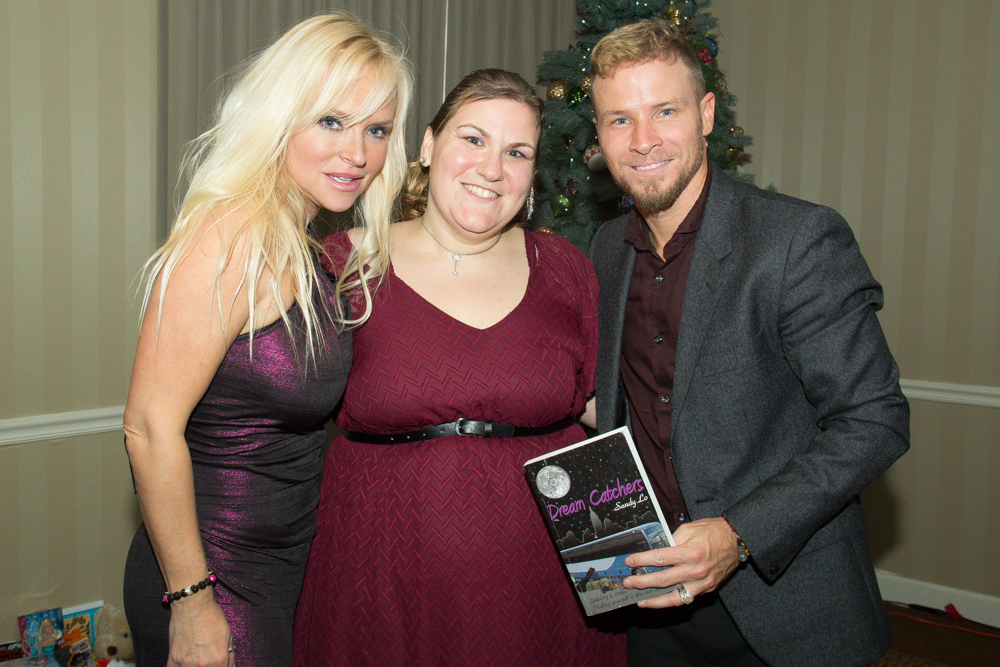 "Sandy Lo (middle) with BSB's Brian Littrell, holding a copy of ""Dream Catchers"", and his wife, Wylee fashion designer, Leighanne. Photo by Kindell Brinay Moore."